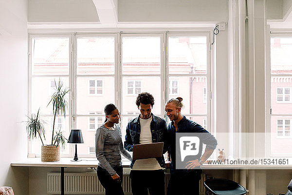 Junger Geschäftsmann hält Laptop in der Hand  während er mit Kollegen am Arbeitsplatz diskutiert