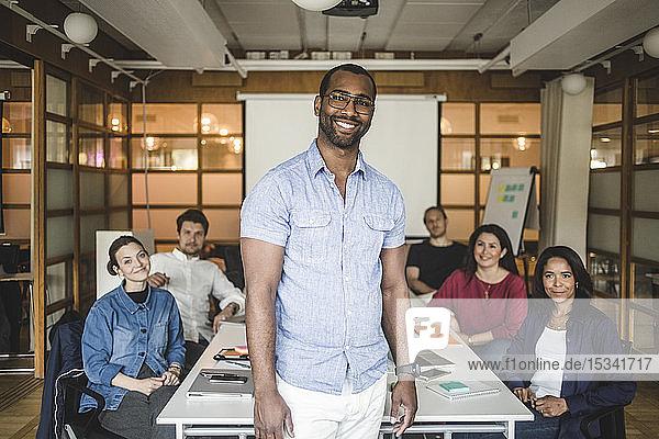Porträt eines selbstbewussten Geschäftsmannes  der seinen Kollegen im Sitzungssaal im Büro zur Seite steht