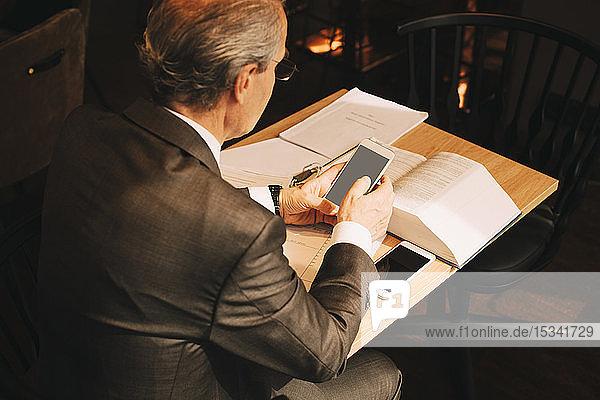 Schrägansicht eines männlichen Anwalts mit einem Smartphone bei der Arbeit in einer Anwaltskanzlei