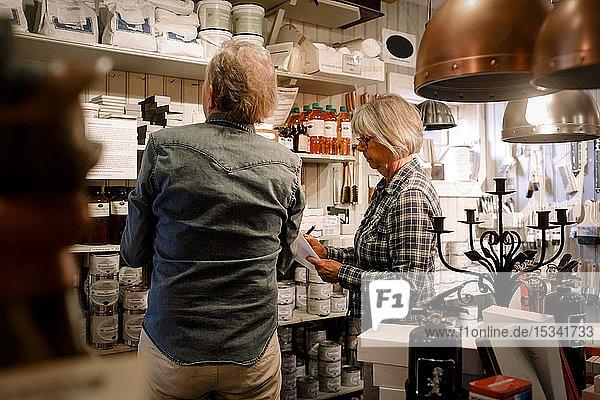 Leitende Mitarbeiter untersuchen Waren  die in Regalen in einem Eisenwarengeschäft angeordnet sind
