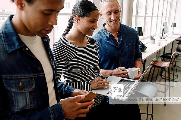 Lächelnde Geschäftsfrau diskutiert mit Kollegen über Laptop im Büro
