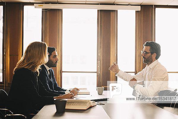 Geschäftsmann erklärt Anwälten Probleme bei Besprechung im Büro