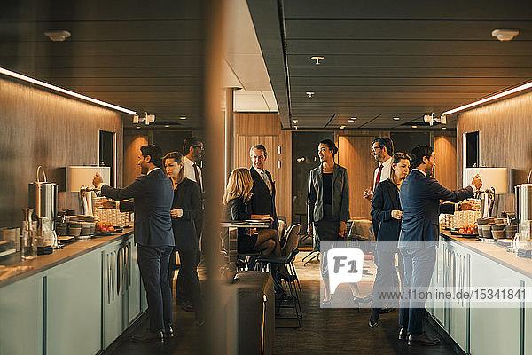 Juristinnen und Juristen sprechen während der Kaffeepause in der Bürokantine