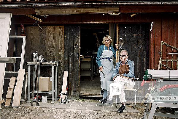 Ganzfiguriges Porträt von lächelnden älteren Mitarbeitern am Eingang zum Baumarkt
