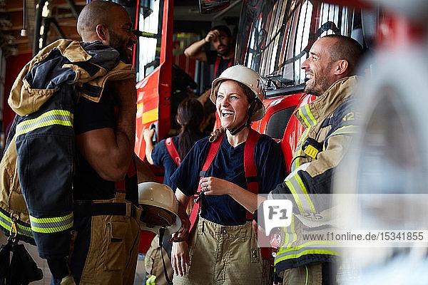 Fröhliche Feuerwehrleute unterhalten sich  während sie in der Feuerwache gegen ein Feuerwehrauto stehen