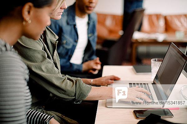 Weibliche Führungskraft benutzt Laptop  während sie mit ihren Kollegen am Schreibtisch im Büro sitzt
