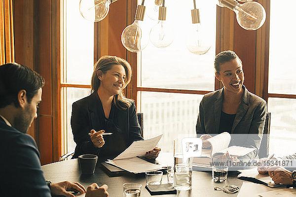 Lächelnde männliche und weibliche Rechtsexperten diskutieren bei einem Treffen im Büro über Dokumente