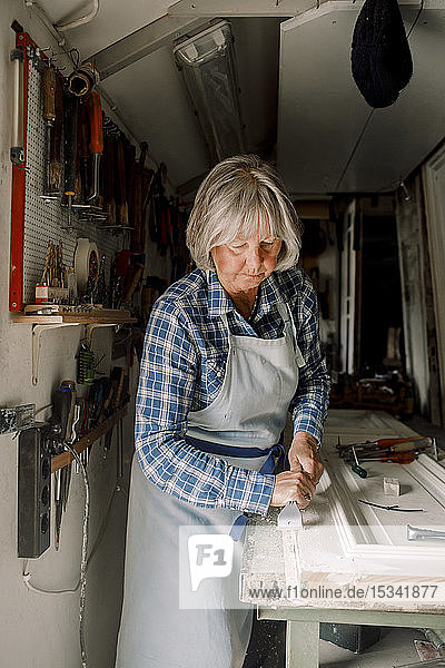 Senior female entrepreneur scraping on window frame at store workshop