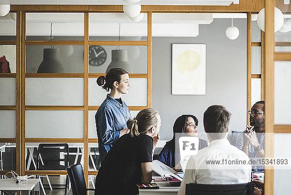 Männliche und weibliche Kollegen planen Geschäftsstrategien bei Treffen im Kreativbüro