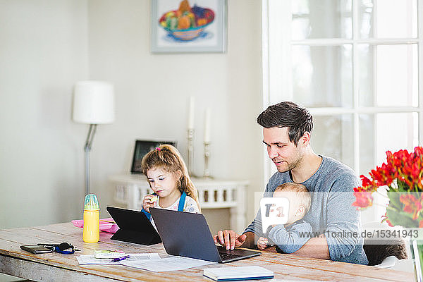 Mid adult man working on laptop while sitting with children at table