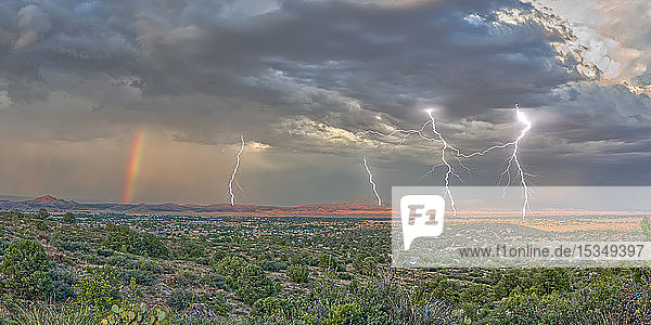A lightning storm with a rainbow rolling over Mingus Mountain just east of Chino Valley  Arizona  United States of America  North America
