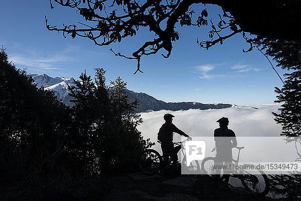 Mountain bikers look out across a valley filled with a cloud inversion in the Himalayas while biking in the Gosainkund region  Langtang region  Nepal  Asia