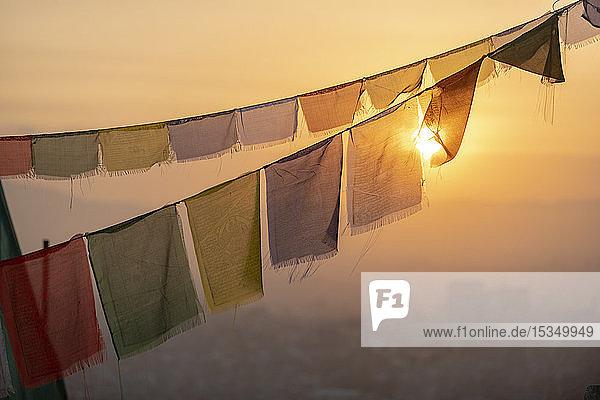 Prayer flags at Swayambhunath (Monkey Temple) in front of the city at sunrise  Kathmandu Valley  Nepal  Asia