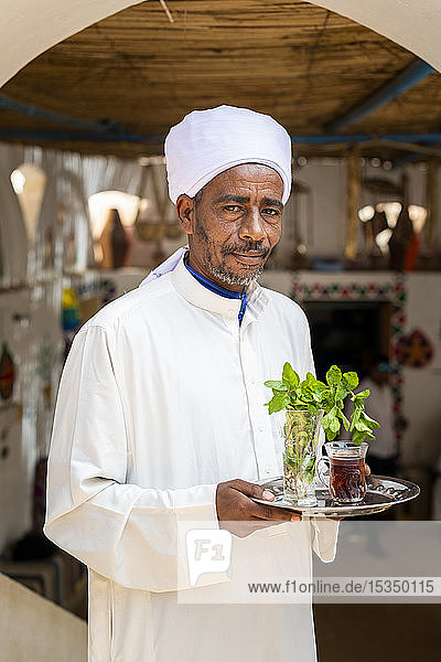 An Egyptian man holds a tray with a glass of mint tea and some fresh mint leaves  Aswan  Egypt  North Africa  Africa