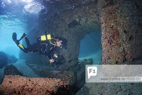 Scuba diver swimming through submerged ancient Roman ruins  Dragonara caves  Miseno  Campi Flegrei (Phlegraean Fields)  Campania  Italy  Europe