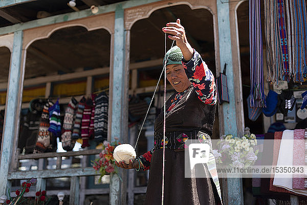 A Sherpa woman from Gosainkund spins baby Yak wool using the traditional method with a spindle  Langtang region  Nepal  Asia