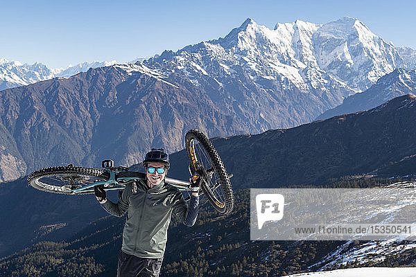 A mountain biker carries his bike up in the Himalayas with views of the Langtang range in the distance  Nepal  Asia