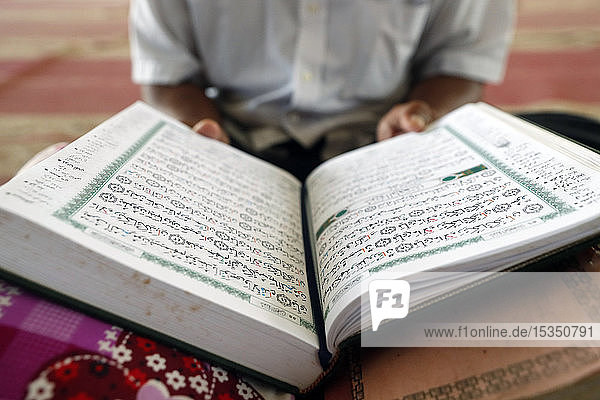 Old man reading Quran sitting on carpet in a mosque  Phnom Penh  Cambodia  Indochina  Southeast Asia  Asia