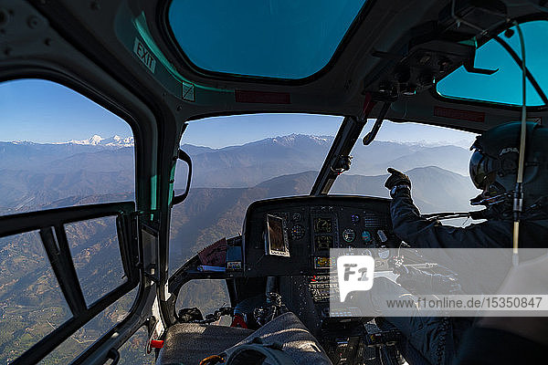 A helicopter flies towards the Himalayas as the pilot points towards the Ganesh Himal range through the window  Langtang region  Nepal  Asia