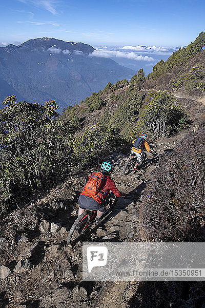 Mountain bikes speed past in a blur along a Enduro style single track trail in the Nepal Himalayas near the Langtang region  Nepal  Asia