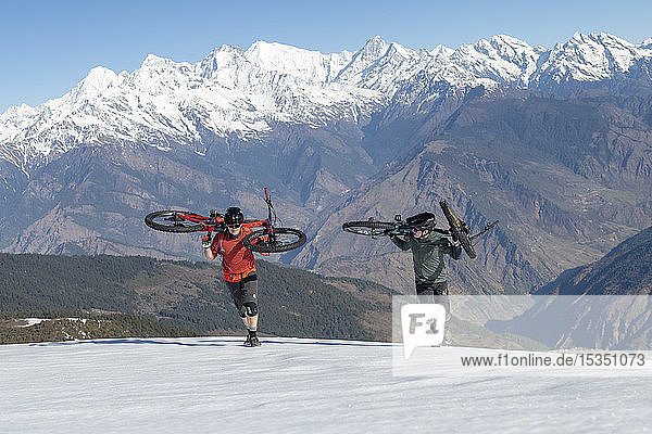 Mountain bikers carry their bikes up a snow covered slope in the Himalayas with views of the Langtang range in the distance  Nepal  Asia