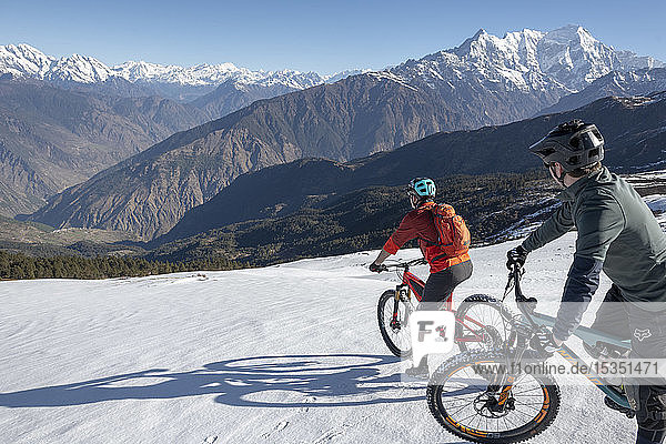 Mountain bikers descend a snow covered slope in the Himalayas with views of the Langtang range in the distance  Nepal  Asia