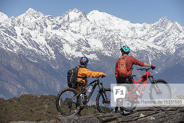 Mountain biking in the Himalayas with views of the Langtang mountain range in the distance  Nepal  Asia