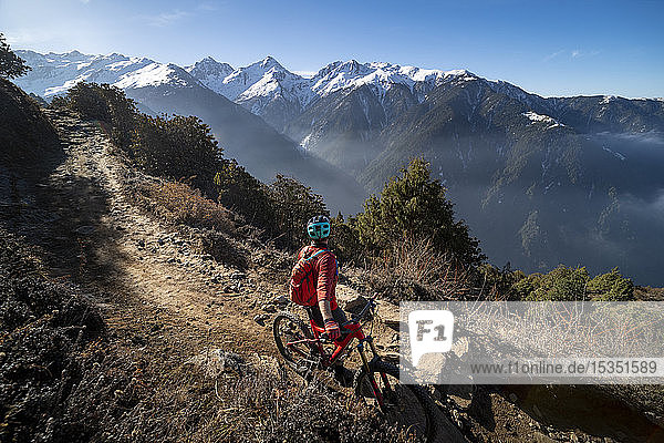 A mountain biker takes a rest on an Enduro style single track trail in the Nepal Himalayas near the Langtang region  Nepal  Asia