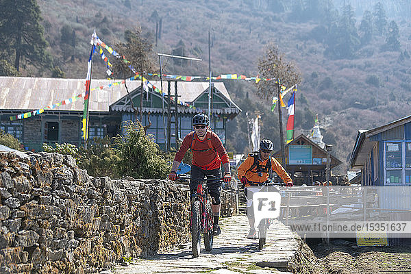 Mountain bikers in the little village of Sing Gompa in the Gosainkund region in the Himalayas  Langtang region  Nepal  Asia