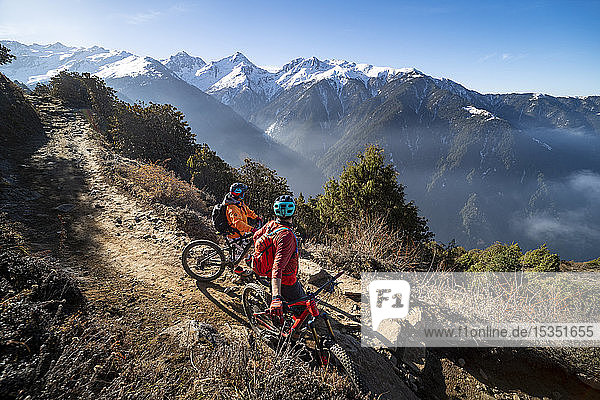 Mountain bikers take a rest on an Enduro style single track trail in the Nepal Himalayas near the Langtang region  Nepal  Asia
