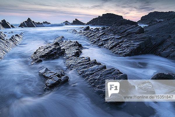 Waves and wet rock ledges at Hartland Quay in North Devon at sunset  Devon  England  United Kingdom  Europe