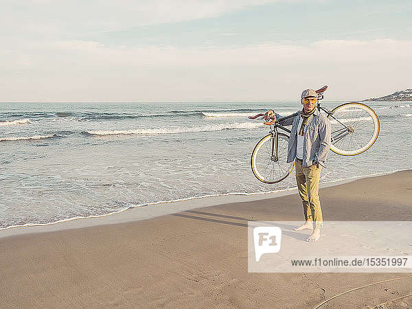 Barefoot man standing with Fixie bike on his shoulder on the beach