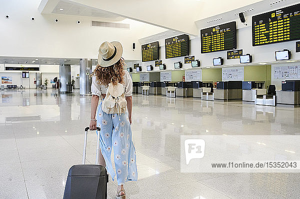 Young woman with baggage at the airport departure hall