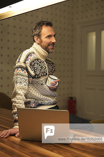 Smiling casual businessman with laptop on table at home