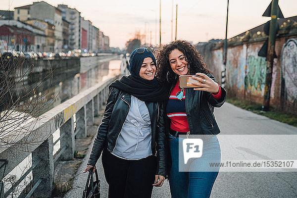 Junge Frau im Hidschab und beste Freundin beim Selfie am Stadtkanal