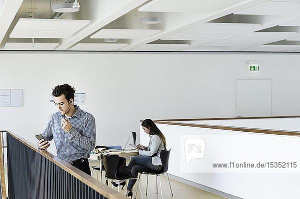 Geschäftsmann mit Smartphone im Bürokorridor  Kollege liest im Hintergrund