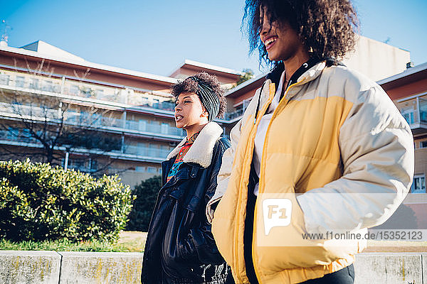 Two cool young female friends on urban sidewalk  side view