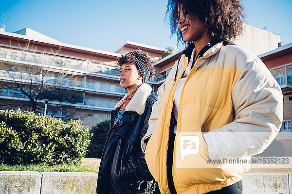Zwei coole junge Freundinnen auf dem städtischen Bürgersteig  Seitenansicht