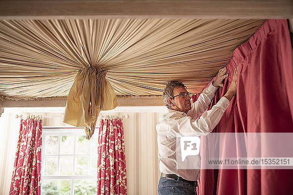 Curtain fitter fitting drapes to four poster bed