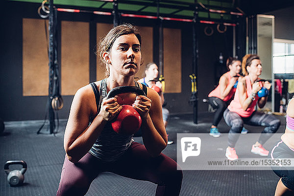 Women training in gym  squatting and lifting kettle bells
