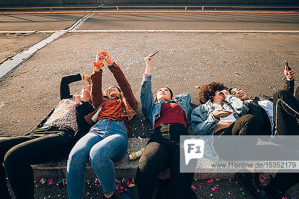 Friends together on kerb taking selfie and using smartphones  Milan  Italy