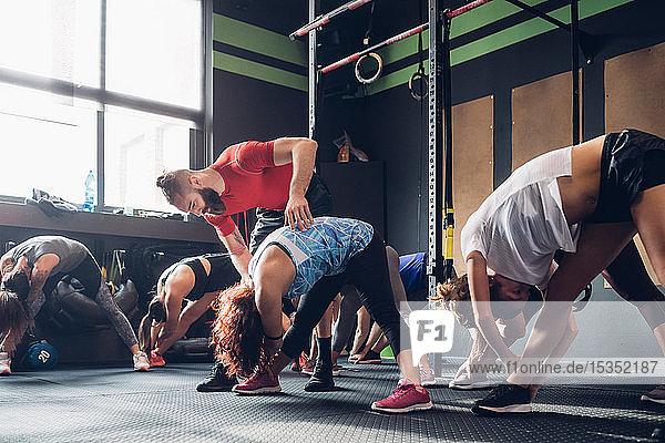 Frauen trainieren in Turnhalle mit männlichem Trainer  Zehen berühren