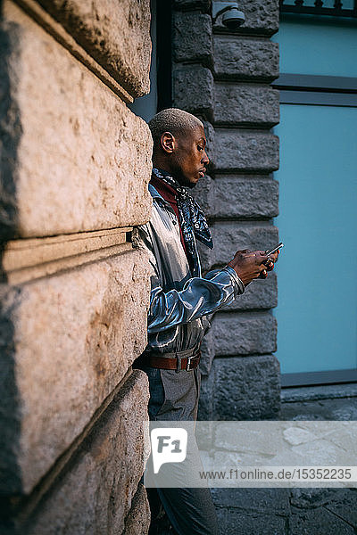 Stylish man using cellphone by period building  Milan  Italy