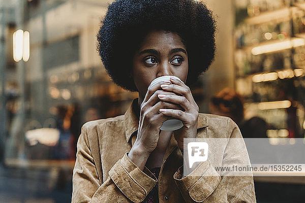 Junge Frau mit Afro-Haaren bei einem Heißgetränk vor einem Café