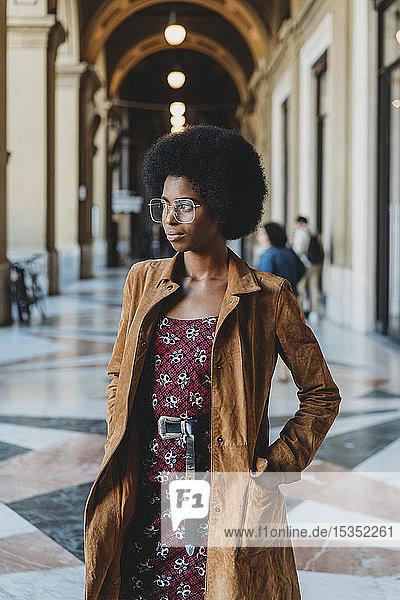 Junge Frau mit Afro-Haaren im Gebäudekorridor