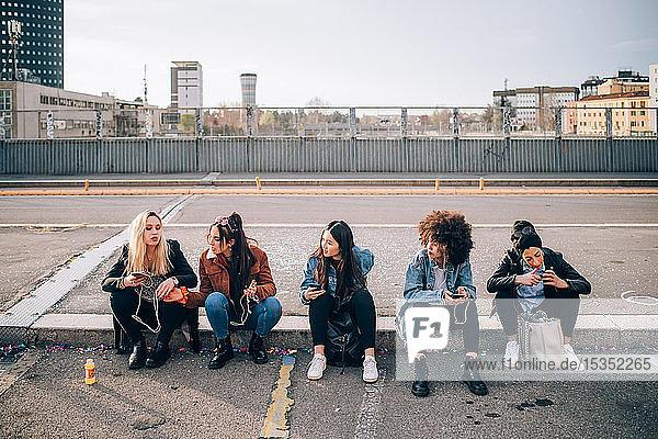 Freunde sitzen mit Smartphone am Bordstein  Mailand  Italien