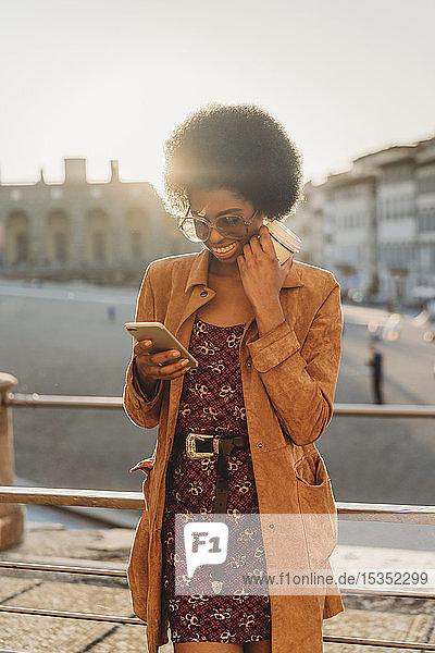 Junge Frau mit Afro-Haaren  die ein Heißgetränk zu sich nimmt und ein Smartphone benutzt  in der Stadt  Florenz  Toskana  Italien
