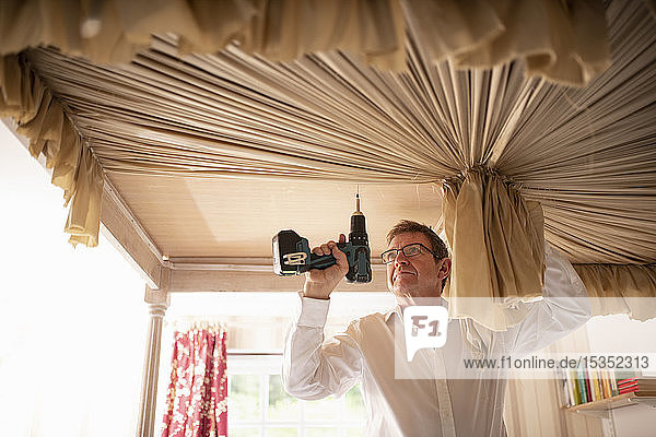 Vorhang-Monteur  der den Baldachin an ein Himmelbett anpasst