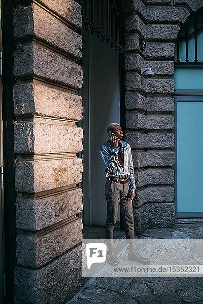 Stilvoller Mann benutzt Handy nach Gebäude der Epoche  Mailand  Italien