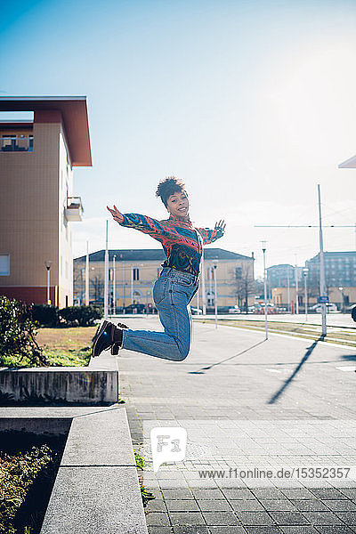Young woman jumping from wall on urban sidewalk  full length portrait